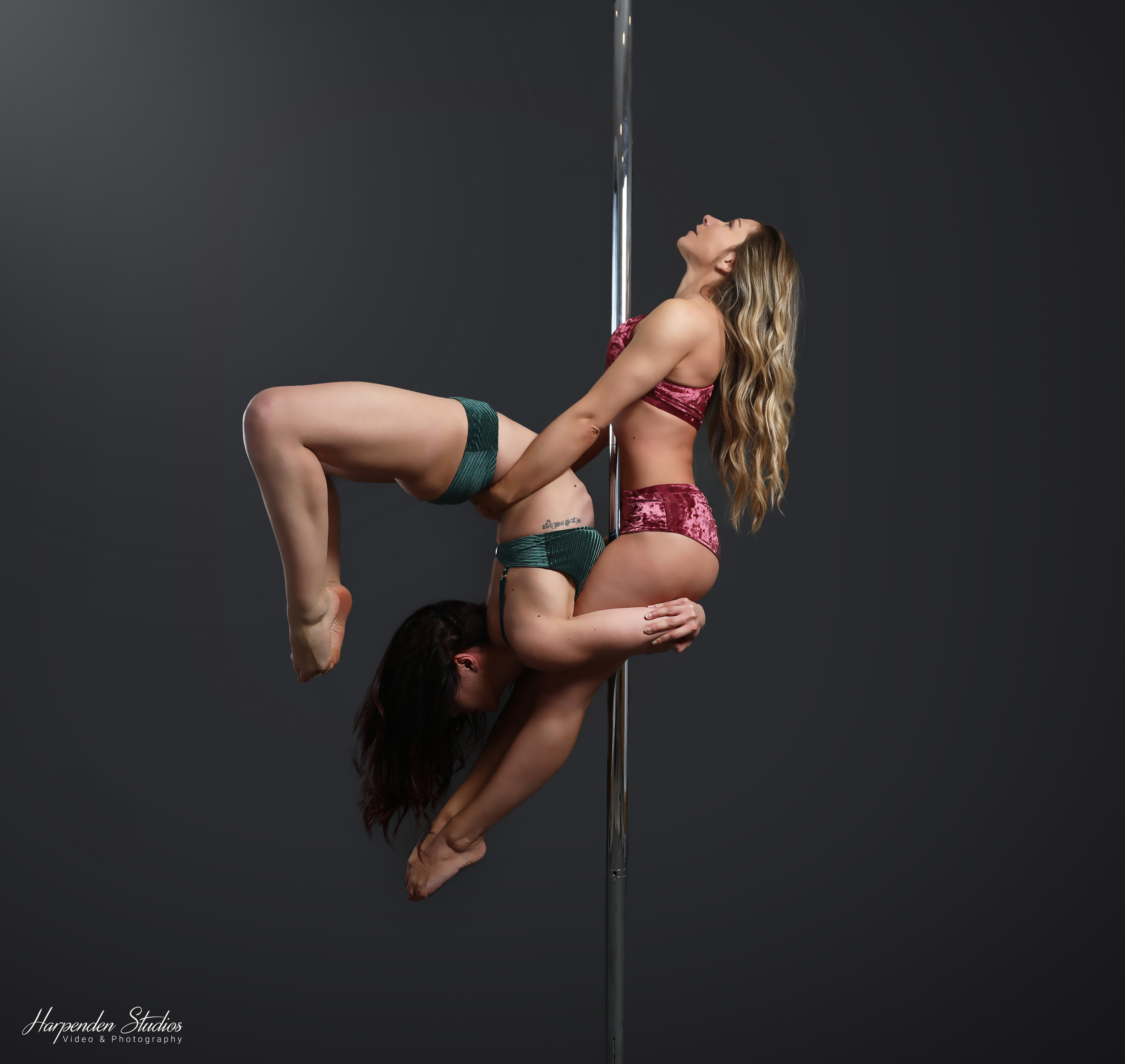 Two women holding a pose during a class at The Pole Hub