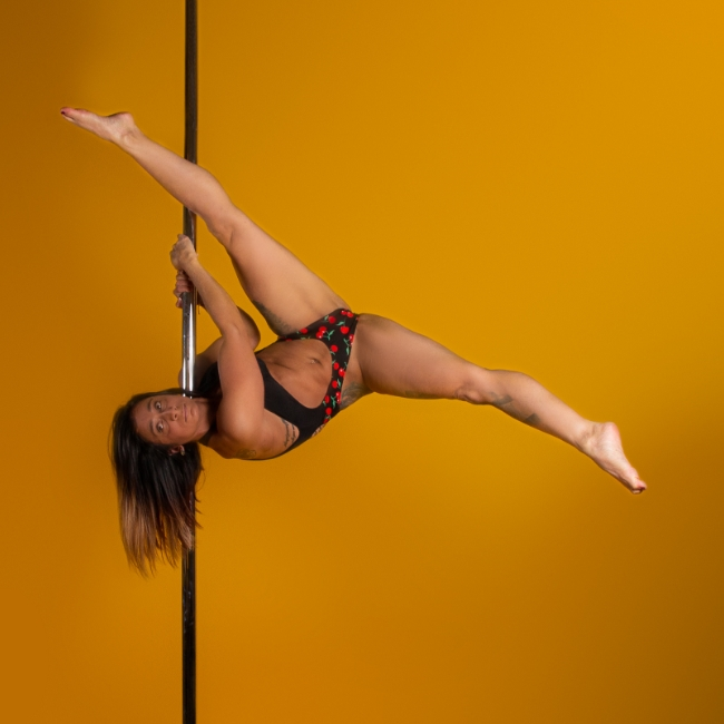 Instructor Carina D holding a pose during a pole fitness class at The Pole Hub