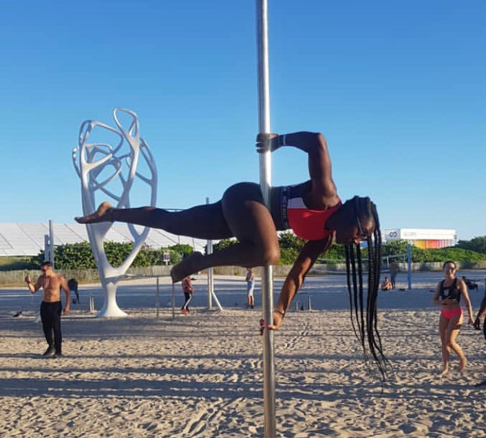 The Pole Hub instructor Chaniqua B-B holding a pose with a pole on a beach