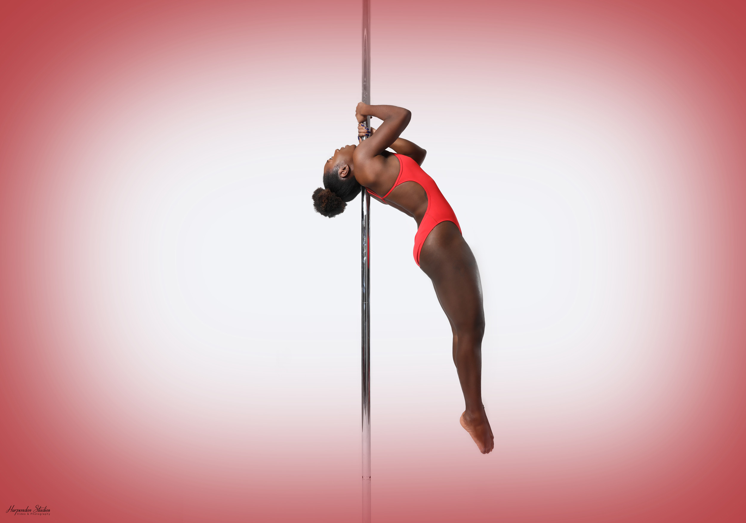 The Pole Hub instructor Chaniqua B-B holding a pose with a pole