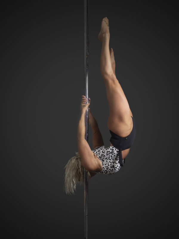 The Pole Hub instructor Dee D holding a pose on a pole