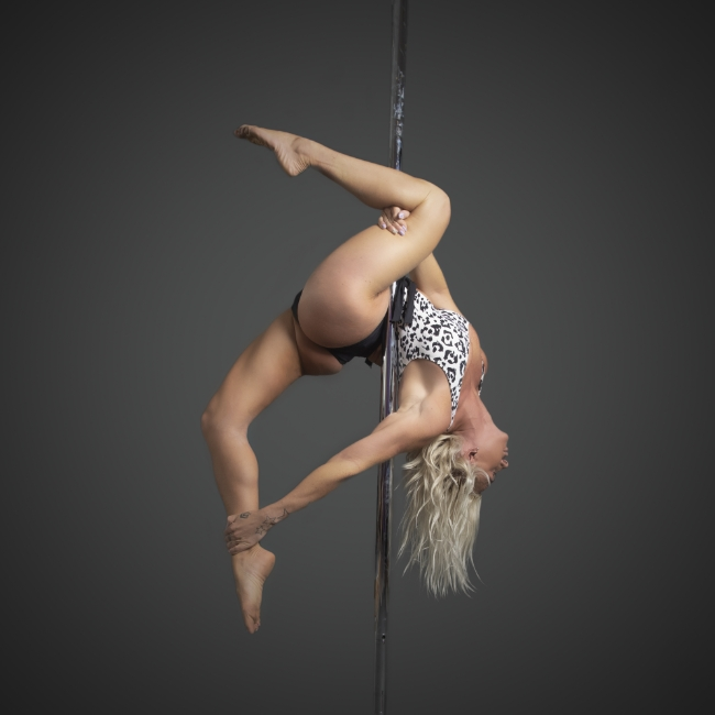 Instructor Dee D holding a pose during a pole fitness class at The Pole Hub