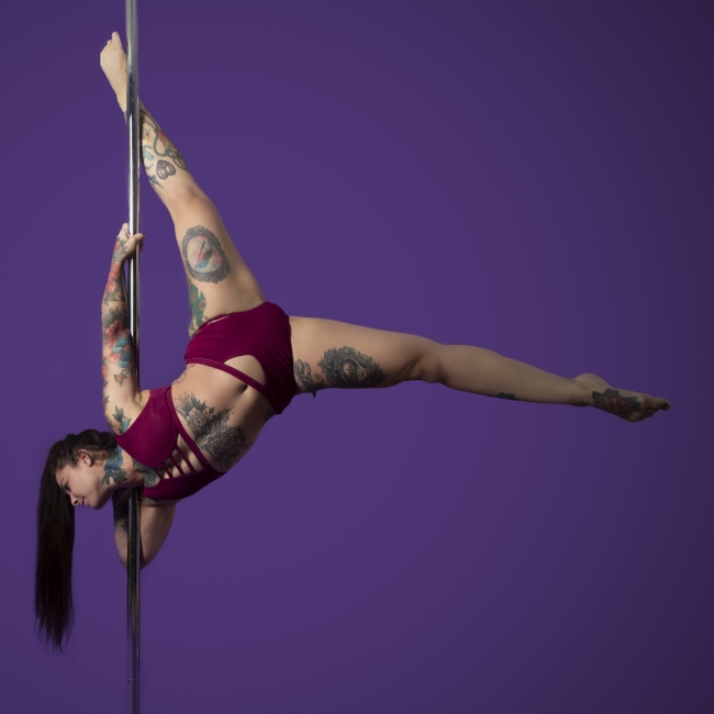 Instructor Fran S holding an Archer pose during a pole fitness class at The Pole Hub