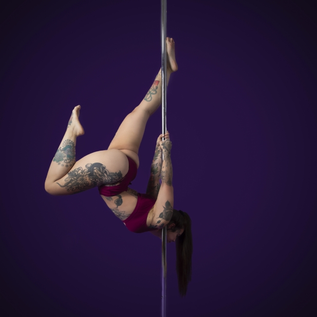 Instructor Fran S holding a Bow & Arrow pose during a pole fitness class at The Pole Hub