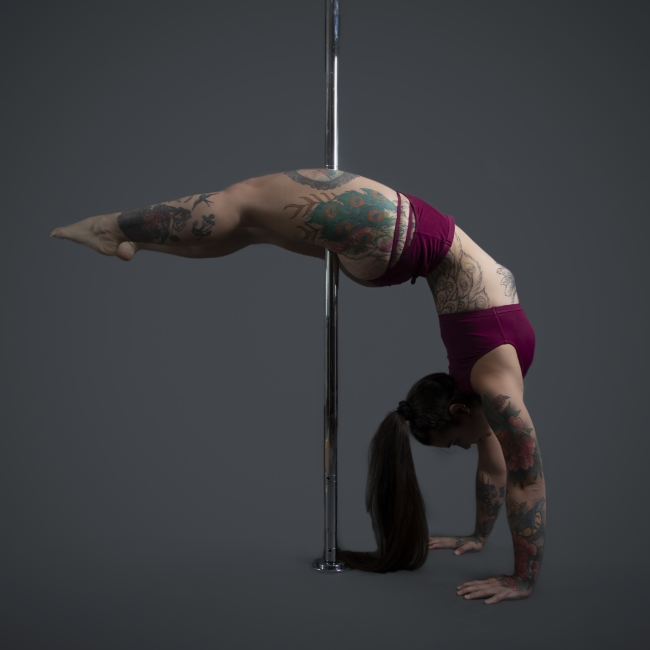 Instructor Fran S holding a Bridge Handstand pose during a pole fitness class at The Pole Hub