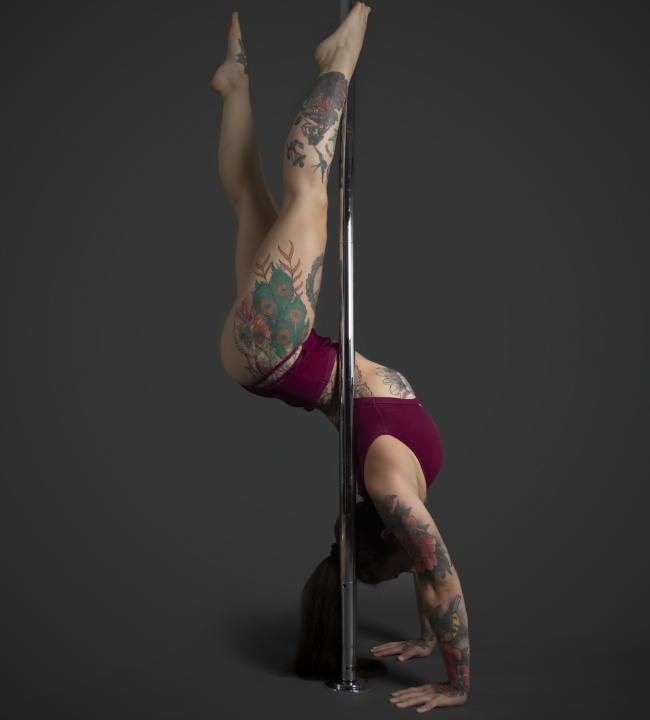 Instructor Fran F holding a Chiropractor pose during a pole fitness class at The Pole Hub