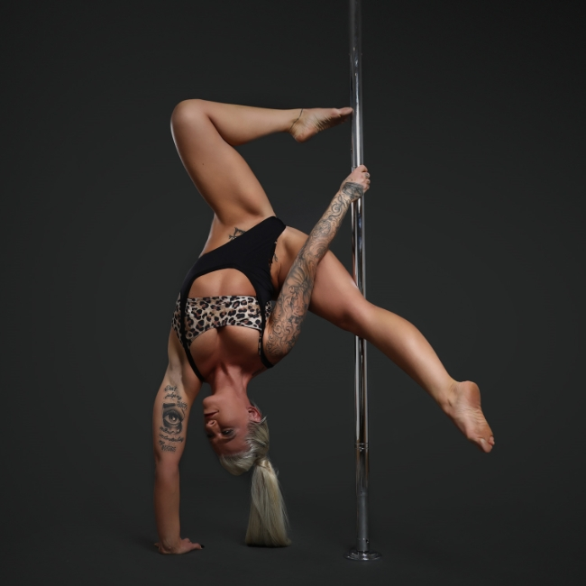 Instructor Helen K holding a pose during a pole fitness class at The Pole Hub