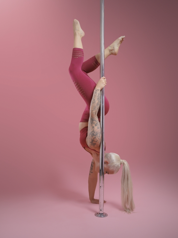The Pole Hub instructor Helen K holding a pose on a pole