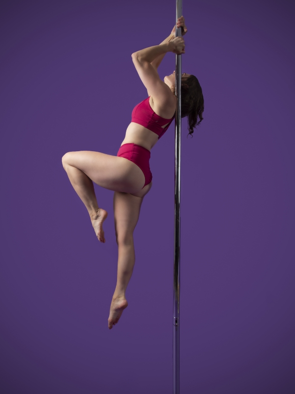 The Pole Hub instructor Kelly K holding a pose on a pole