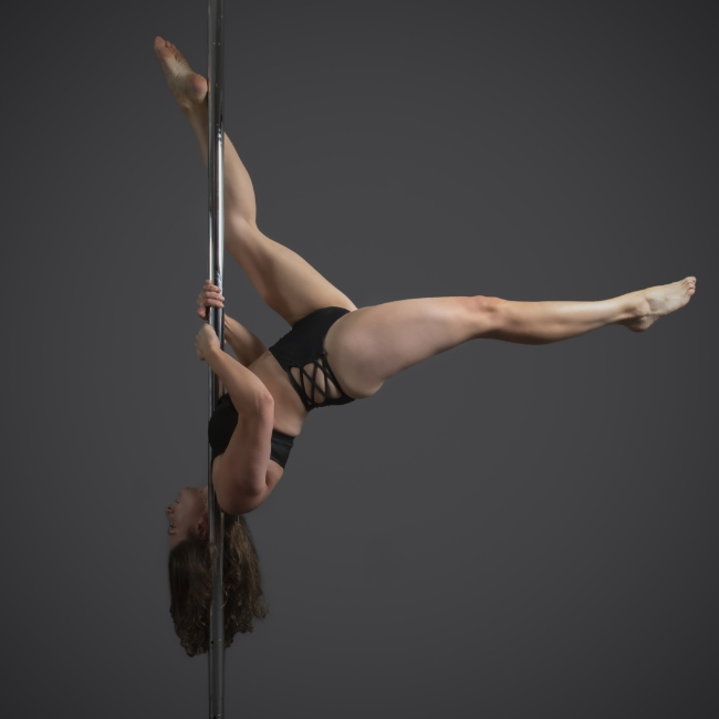 Instructor Kelly K holding a pose during a pole fitness class at The Pole Hub