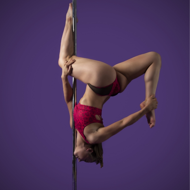 Instructor Lily G holding a no-handed butterfly pose during a pole fitness class at The Pole Hub