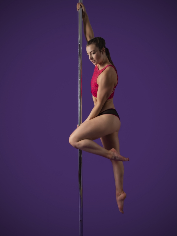 The Pole Hub instructor Lily G holding a pose on a pole