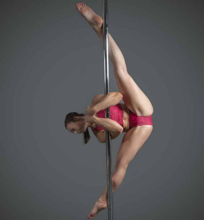 Instructor Lily G holding the box pose during a pole fitness class at The Pole Hub