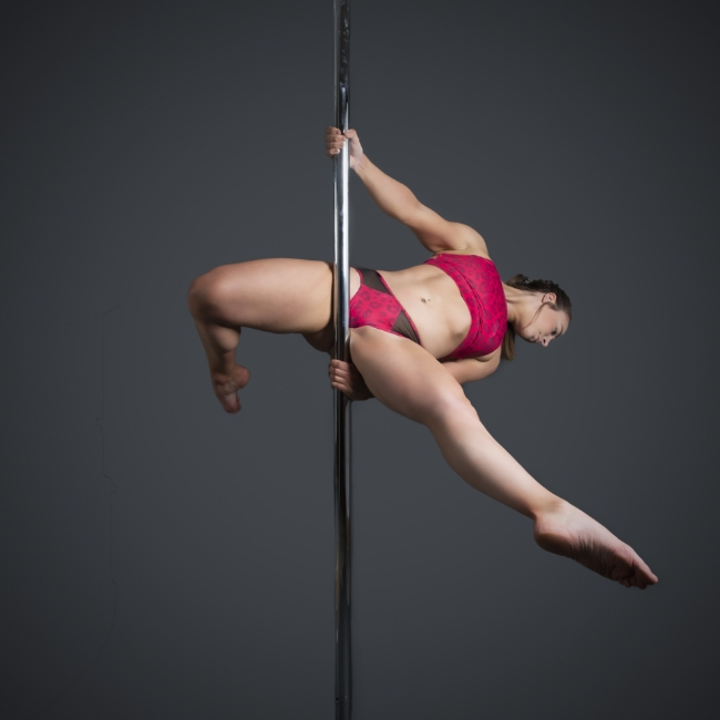Instructor Lily G holding a wristseat pose during a pole fitness class at The Pole Hub