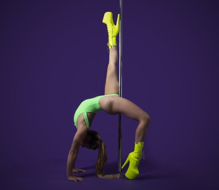 Instructor Viktoria F holding a pose during a pole fitness class at The Pole Hub