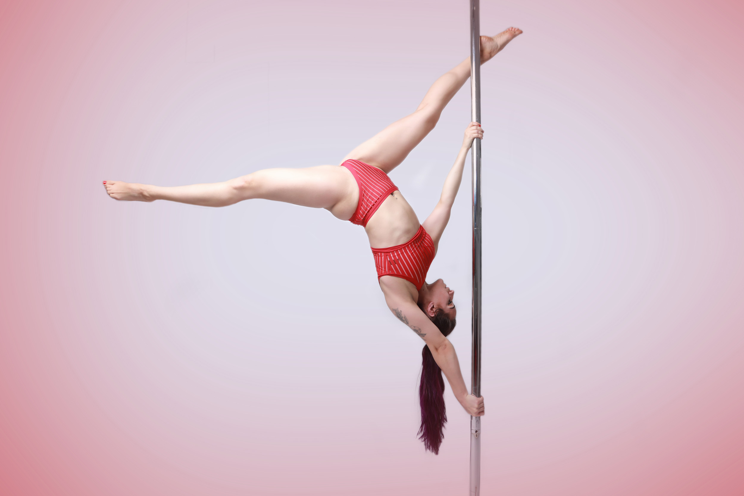 The Pole Hub instructor Viktoria F holding a pose on a pole