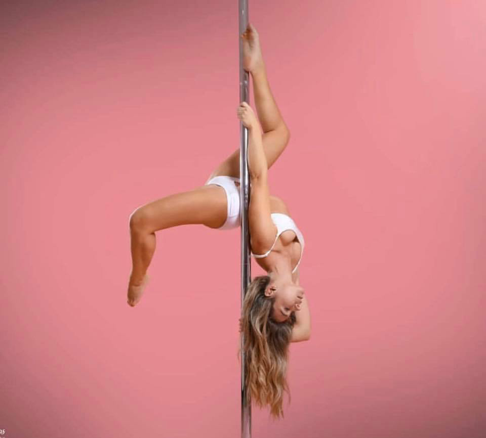 One woman holding a pose during a pole fitness class at The Pole Hub